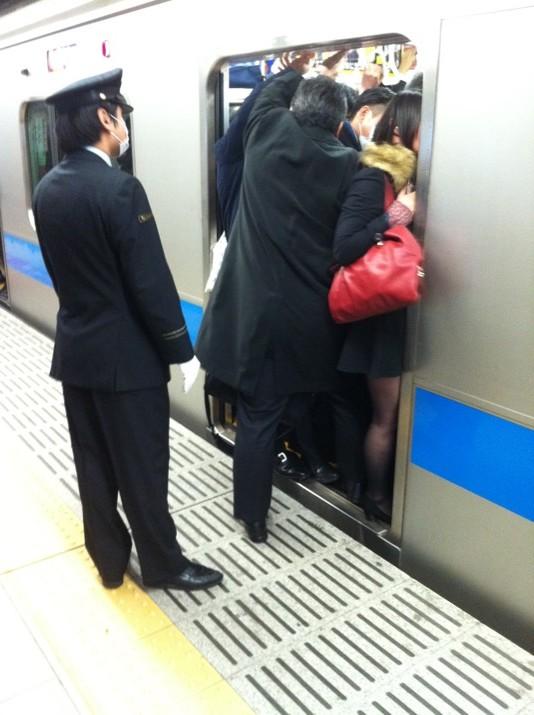 Secuencia de fotos de empujadores en el metro de la mañana class=